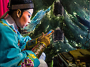 08 DECEMBER 2016 - BANGKOK, THAILAND: A cast member plays video games on his smart phone before going on stage during a Chinese opera (also called ngiew in Thailand) performance at Pek Leng Keng Shrine in the Khlong Toei neighborhood of Bangkok. Public performances of music and celebration were banned during the first 30 days of the mourning period for Bhumibol Adulyadej, the Late King of Thailand. Now, nearly two months after the revered monarch's death, Bangkok street life is returning to normal and Chinese temples and shrines are once again scheduling operas.      PHOTO BY JACK KURTZ