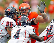 Virginia Cavaliers defensive tackle Brent Urban (99) is blocked by Richmond Spiders offensive linesman Austin Gund (66) and Richmond Spiders running back Jovan Smith (4) during the first half of the NCAA football game Saturday September, 1, 2012 at Scott Stadium in Charlottesville, Va.