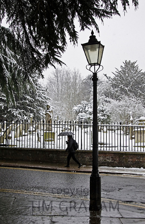 Woman with umbrella walks past snow covered graveyard, Hampstead, North London, United Kingdom