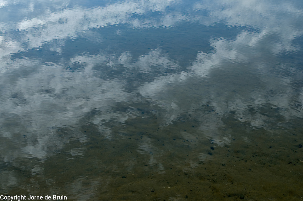 A reflection of a clouded sky in a still tidal pool at the beach, Texel. the Netherlands