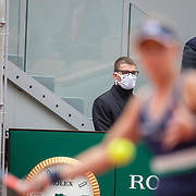 PARIS, FRANCE October 08.  A ball boy and security staff wearing masks watch Nadia Podoroska of Argentina in action against Iga Swiatek of Poland in the Semi Finals of the singles competition on Court Philippe-Chatrier during the French Open Tennis Tournament at Roland Garros on October 8th 2020 in Paris, France. (Photo by Tim Clayton/Corbis via Getty Images)
