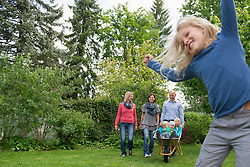 Young family playing in garden with wheelbarrow