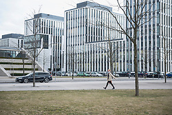 Side profile of a young woman walking in city road with high rise buildings in city, Munich, Bavaria, Germany