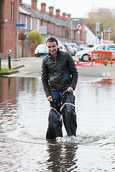 © Licensed to London News Pictures. 09/02/2014. Winchester, Hampshire, UK. A man wearing an improvised pair of waders made from bin liners whilst he helps his friend retrieve their flooded car on Park Avenue in Winchester. Water levels rose overnight in parts of the historic city where a flood warning has been issued by the Environment Agency for parts of the River Itchen. Photo credit : Rob Arnold/LNP