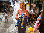 27 AUGUST 2016 - BANGKOK, THAILAND: Her daughter runs towards a snack shop while a woman hangs her laundry to dry in the Pom Mahakan slum community. The Pom Mahakan community is known for fireworks, fighting cocks and bird cages. Mahakan Fort was built in 1783 during the reign of Siamese King Rama I. It was one of 14 fortresses designed to protect Bangkok from foreign invaders. Only two of the forts are still standing, the others have been torn down. A community developed in the fort when people started building houses and moving into it during the reign of King Rama V (1868-1910). The land was expropriated by Bangkok city government in 1992, but the people living in the fort refused to move. In 2004 courts ruled against the residents and said the city could evict them. The city vowed to start the evictions on Sept 3, 2016, but this week Thai Prime Minister Gen. Prayuth Chan-O-Cha, sided with the residents of the fort and said they should be allowed to stay. Residents are hopeful that the city will accede to the wishes of the Prime Minister and let them stay.       PHOTO BY JACK KURTZ