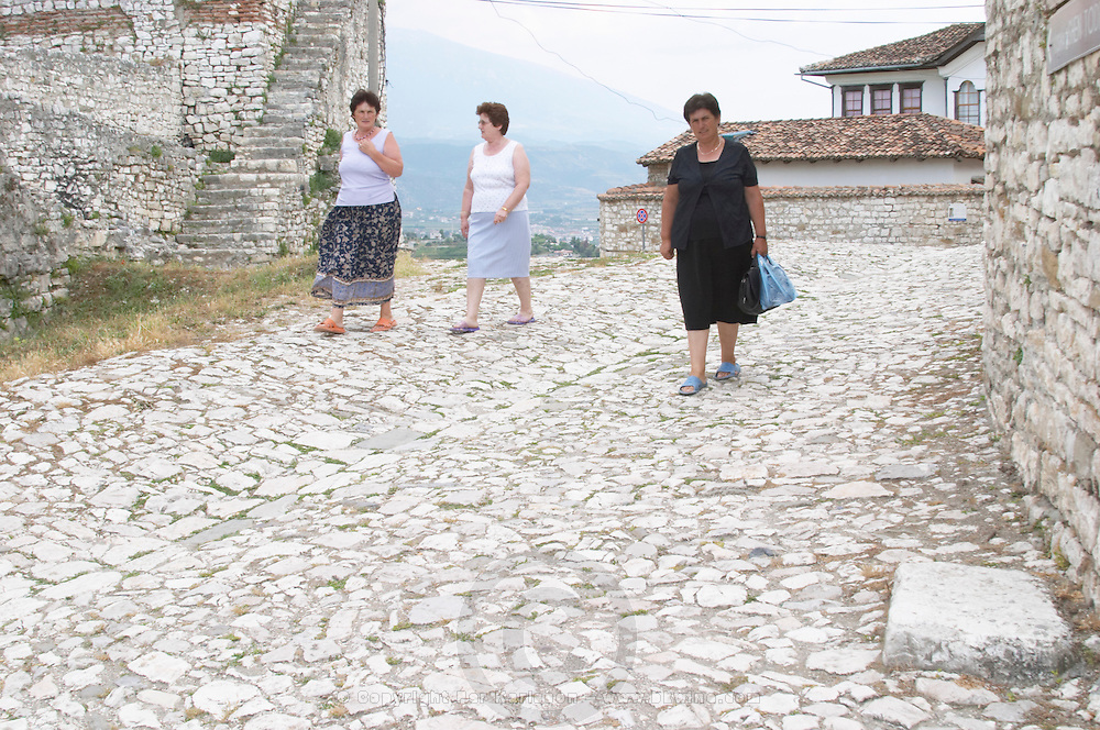 Albanian women living in the old town walking on a cobble stone street. Berat upper citadel old walled city. Albania, Balkan, Europe.