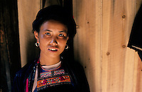Taking a break from her housework a young woman of the Dong ethnic minority group at home in Guizhou province, southern China.