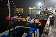 Fishing buoys are attached to the rear of a boat moored in a North Sea town harbour, with its dock at night behind, on 25th September 2017, in Amble, Northumberland, England.
