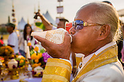 06 JANUARY 2013 - BANGKOK, THAILAND:  A Brahmin priest blows a conch shell horn during a prayer service for a relic of the Buddha's hair in Bangkok. The relic has been on display in Bangkok for about 10 years. There was a ceremony in Sanam Luang in Bangkok Sunday to honor the relic. People prayed for it and received blessings from Buddhist monks and Brahmin priests who presided over the service. The hair is being moved to Ayutthaya, where it will be displayed in a Buddhist temple. The piece of hair has been on loan to Thai Buddhists from a Buddhist temple in Sri Lanka.   PHOTO BY JACK KURTZ