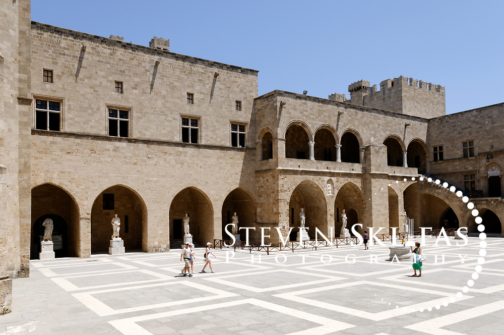 Rhodes. Greece. Palace of the Grand Masters central courtyard at Rhodes old town. The courtyard is paved with geometric marbles tiles and lined with ancient Hellenistic statues at Rhodes old town. Dating from the 14th century, the Palace of the Grand Masters is a fortress within the old town that was seat of government of the Grand Masters and nerve centre of the Knights quarter. It was restored in the 1930's by Italians for the intention of using it as a summer residence for Mussolini.