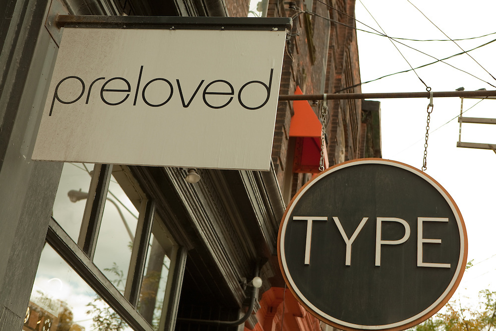 Shop signs for Preloved, a boutique selling garments fashioned from recycled fabrics, and Type, an independent bookstore, on Toronto's trendy Queen Street West.