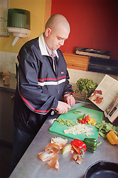 Male resident preparing communal meal in kitchen of homeless hostel for people with learning difficulties,
