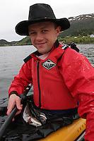 Mann har fisket en liten sei (Pollachius virens) og en liten lyr (pollachius pollachius) på dorg fra kajakk i Aursundet, a man has just been fishing a small coalfish and a pollac with a trolling line from kayak