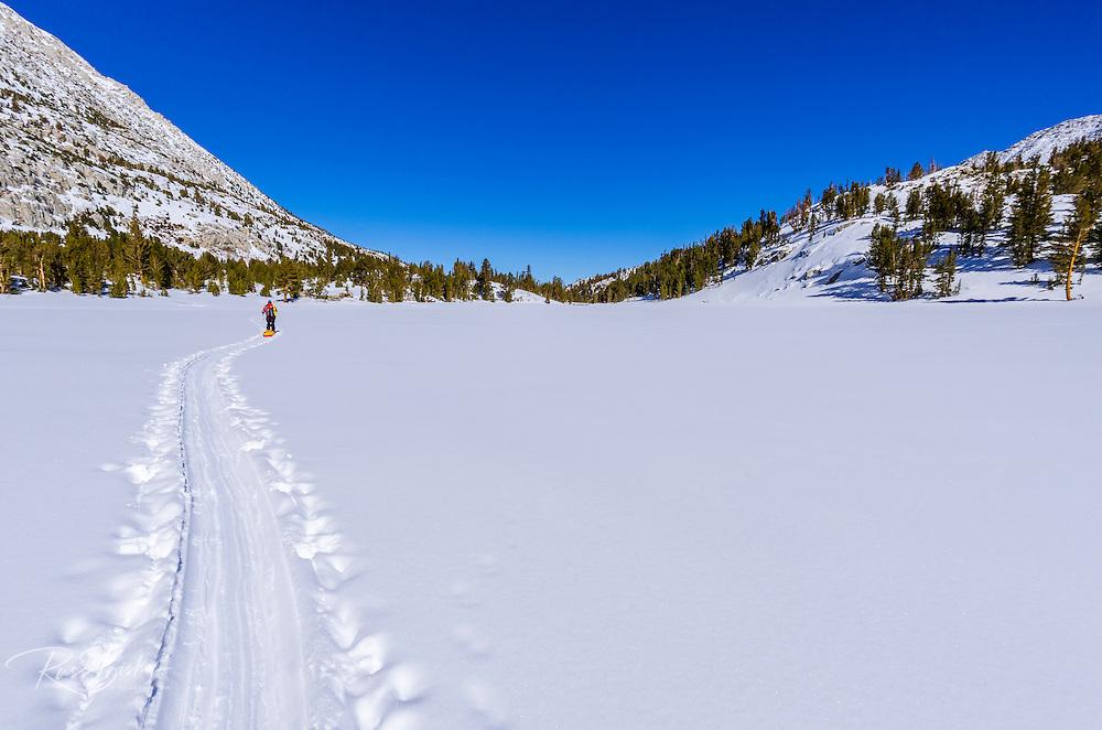 Backcountry skier crossing Heart Lake, John Muir Wilderness, Sierra Nevada Mountains, California  USA