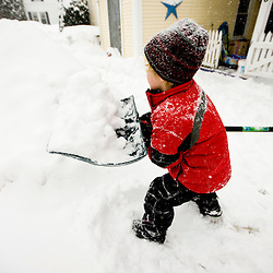 A young boy (age 5) shovels snow during a snowstorm in Portsmouth, New Hampshire.