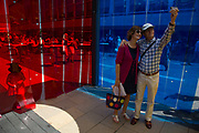 Summertime in London, England, UK. Time for a selfie as people interact with small rooms made from coloured plastic in red and blue as part of the Southbank Centre's Festival of Love. This is an arts and activities festival based in and around the South Bank and Royal Festival Hall.