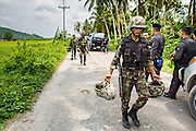 08 JULY 2013 - MAYO, PATTANI, THAILAND:  A Thai soldier, carrying the helmets of his colleagues wounded in an IED blast, walks back to his vehicle after clearing the scene in Pattani province Monday. Eight Thai soldiers were injured - one seriouly and seven with minor injuries - when their truck was hit by an IED outside Mayo, Pattani province in southern Thailand Monday. The soldiers were returning from a teacher protection mission when their truck ran over the explosive. The attack was thought to be conducted by Muslim insurgents who have been battling the Thai government for greater autonomy. The conflict in southern Thailand has claimed about 5,000 lives since 2004.   PHOTO BY JACK KURTZ