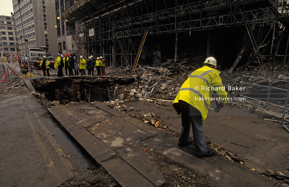 Two days after the Irish Republican Army (IRA) exploded a truck bomb on Bishopsgate, a main arterial road that travels north-south through London's financial area, City of London engineering officials examine the huge crater left by the terrorist device, on 26th April 1993, in London, England.  Debris is strewn around the hole with drainage and road material. It was said that Roman remains could be viewed at the bottom of the pit the bomb created. One person was killed when the one ton fertiliser bomb detonated directly outside the medieval St Ethelburga's church. Buildings up to 500 metres away were damaged, with one and a half million square feet (140,000 m²) of office space being affected and over 500 tonnes of glass broken. Costs of repairing the damage was estimated at £350 million. It was possibly the (IRA's) most successful military tactic since the start of the Troubles.