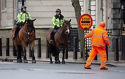 © Licensed to London News Pictures. 12/01/2021. London, UK. Mounted police officers patrol through Whitehall in London past a construction worker with a stop go sign. The construction industry faces criticism for contributing to the spread of Covid 19 by its being allowed to continue operating during lockdown. Photo credit: London News Pictures.