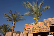 An old advert for Kodak film beneath palm tree inside the enclosure of the ancient Egyptian remains of Karnak in modern Luxor, Nile Valley, Egypt.