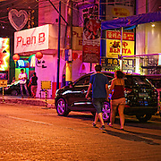 A couple walks the streets in the Makati Red Light District
