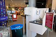 Nederland, Berg en Dal, 17-3-2020  In deze Plus supermarkt wordt klanten gevraagd om eerst hub handen te ontsmetten bij de ingang van de winkel . Er wordt handgel aangeboden en een kraan met zeep . Dit gebeurd ook om het eigen personeel te beschermen tegen het besmetten door klanten . Foto: Flip Franssen
