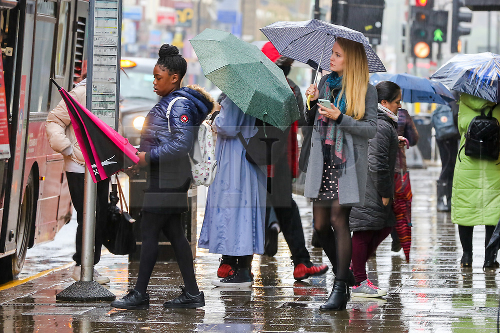 © Licensed to London News Pictures. 21/10/2020. London, UK. Members of the public shelter from rain underneath umbrellas at a bus stop in north London. According to the Met Office, heavy rain and strong winds are forecast later today from Storm Barbara. Photo credit: Dinendra Haria/LNP