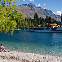 """Wakatipu beach and the TSS Earnslaw with the Remarkables mountain range in the background. According to """"Wikipedia"""" - The TSS Earnslaw is a 1912 Edwardian vintage twin screw steamer plying the waters of Lake Wakatipu in New Zealand. It is one of the oldest tourist attractions in Central Otago, and the only remaining commercial passenger-carrying coal-fired steamship in the southern hemisphere."""