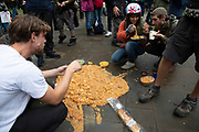 Extinction Rebellion eat vegan food off the road as disruption begins and the activists block 12 sites around Westminster on 7th October 2019 in London, England, United Kingdom. Extinction Rebellion is a climate change group started in 2018 and has gained a huge following of people committed to peaceful protests. These protests are highlighting that the government is not doing enough to avoid catastrophic climate change and to demand the government take radical action to save the planet.