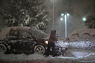 Middletown, New York  - A woman clears the snow off the hood of her car during a snowstorm on Oct. 29, 2011.