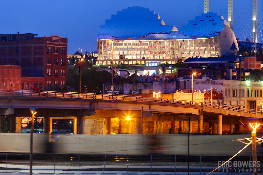 Kansas City's Kauffman Center for the Performing Arts at dusk with view of Crossroads District and train motion blur in foreground - taken from Washington Square Park.