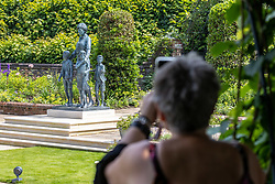 Licensed to London News Pictures. 02/07/2021. London, UK. Members of the public enjoy seeing the Diana, Princess of Wales statue by sculpture Ian Rank-Broadley for the first time at Kensington Palace, London today. The bronze statue has gone on show to the public in the Sunken Garden at Kensington Palace today after it was unveiled yesterday by her sons HRH Prince William and Prince Harry on what would have been her 60th birthday. Photo credit: Alex Lentati/LNP