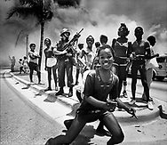 Curious children stand by Florida National Guardsmen who are attempting to deter any further violence during the 1980 McDuffie riots in Liberty City, Miami.