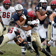 NEW HAVEN, CONNECTICUT - NOVEMBER 18: Running back Zane Dudek #33 of Yale is tackled by Charlie Walker #41 of Harvard and Tanner Lee #36 of Harvard during the Yale V Harvard, Ivy League Football match at the Yale Bowl. Yale won the game 24-3 to win their first outright league title since 1980. The game was the 134th meeting between Harvard and Yale, a historic rivalry that dates back to 1875. New Haven, Connecticut. 18th November 2017. (Photo by Tim Clayton/Corbis via Getty Images))