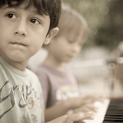 a young french boy plays music on an keyboard along wiht his friends on a sunday afternoon in new delhi