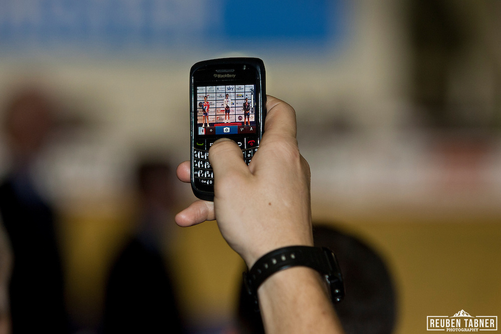 A journalist takes a photograph of the medal presentation's at the UCI Track Cycling World Cup on his Blackberry.