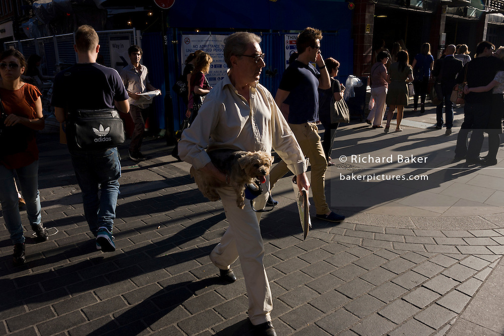 Male dog owner carries his beloved pet over a road in central London.