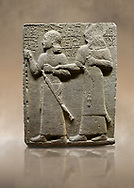 """Photo of Hittite monumental relief sculpted orthostat stone panel of Royal Buttress. Basalt, Karkamıs, (Kargamıs), Carchemish (Karkemish), 900-700 B.C. Anatolian Civilisations Museum, Ankara, Turkey.<br /> <br /> King Araras holds his son Kamanis from the wrist. King carries a sceptre in his hand and a sword at his waist while the prince leans on a stick and carries a sword on his shoulder. <br /> <br /> Hieroglyphs reads; """"This is Kamanis and his siblings. I held his hand and despite the fact that he is a child, I located him on the temple. This is Yariris' image"""".  <br /> <br /> Against a brown art background. .<br />  <br /> If you prefer to buy from our ALAMY STOCK LIBRARY page at https://www.alamy.com/portfolio/paul-williams-funkystock/hittite-art-antiquities.html  - Type  Karkamıs in LOWER SEARCH WITHIN GALLERY box. Refine search by adding background colour, place, museum etc.<br /> <br /> Visit our HITTITE PHOTO COLLECTIONS for more photos to download or buy as wall art prints https://funkystock.photoshelter.com/gallery-collection/The-Hittites-Art-Artefacts-Antiquities-Historic-Sites-Pictures-Images-of/C0000NUBSMhSc3Oo"""