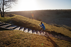 © Licensed to London News Pictures. 16/02/2014. Winchester, Hampshire, UK. A Cross Training runner tackling steps to St. Catherine's Hill near Winchester at sunrise this morning, 16th February 2014. The welcomed sunshine offers respite to the seemingly never ending stormy period experienced in the UK. Photo credit : Rob Arnold/LNP
