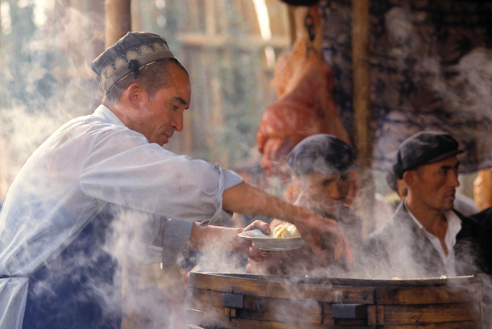 A food vendor is shrouded by steam as he serves lunch to the gathered crowd in Kashgar, Xinjiang, China.