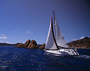 A sailboat coasts through carribean waters off of the British Virgin Islands