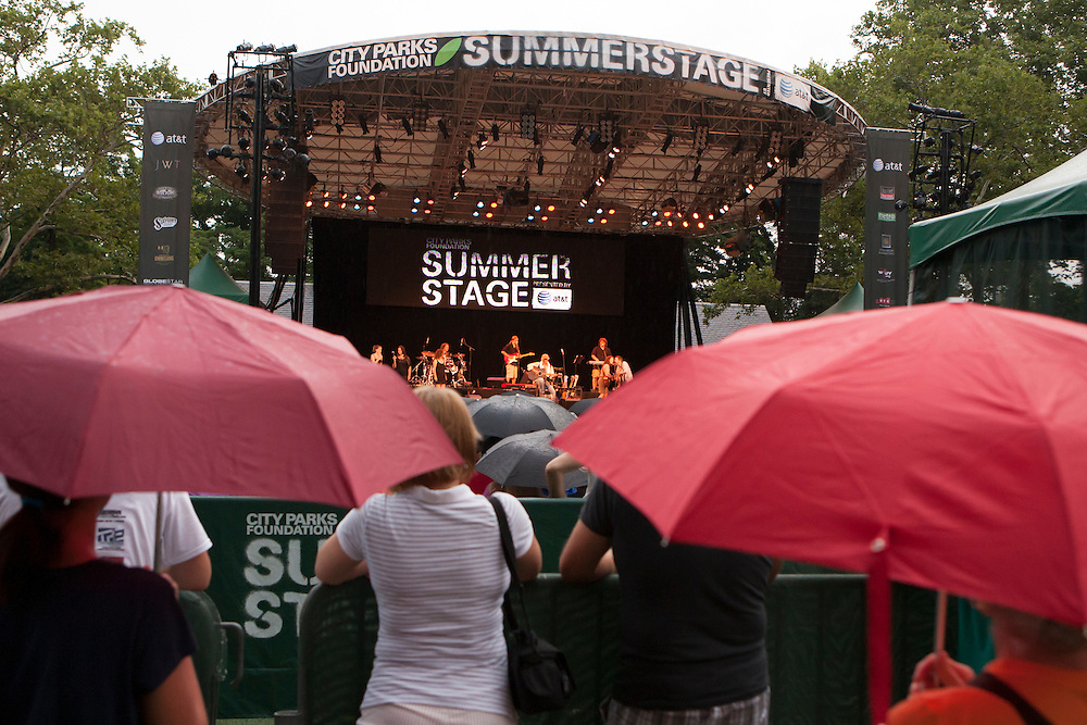 Spectators, some under umbrellas, watch in the rain.