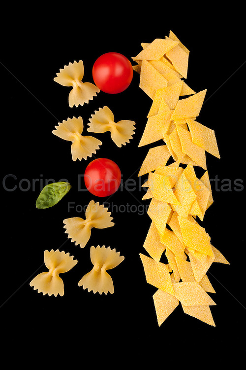 Dry Pasta Assortment - Farfalle and maltagliati, cherry tomato and basil leaf, isolated on black  background.