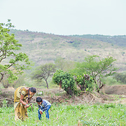 INDIVIDUAL(S) PHOTOGRAPHED: Sonali Tulpule (left) and Ganesh Tulpule (right). LOCATION: Ahirwade, Maharashtra, India. CAPTION: Sonali (left) and her nephew Ganesh (right) tend to a small plot of land on their family farm. While many people across India are heavily dependent on chemical fertilisers, this family is able to use bio-slurry, a by-product from the biogas unit they recently had installed by Sistema Biobolsa. This simple technology ferments organic waste and turns it into methane gas, which the family is then able to use instead of firewood for cooking.