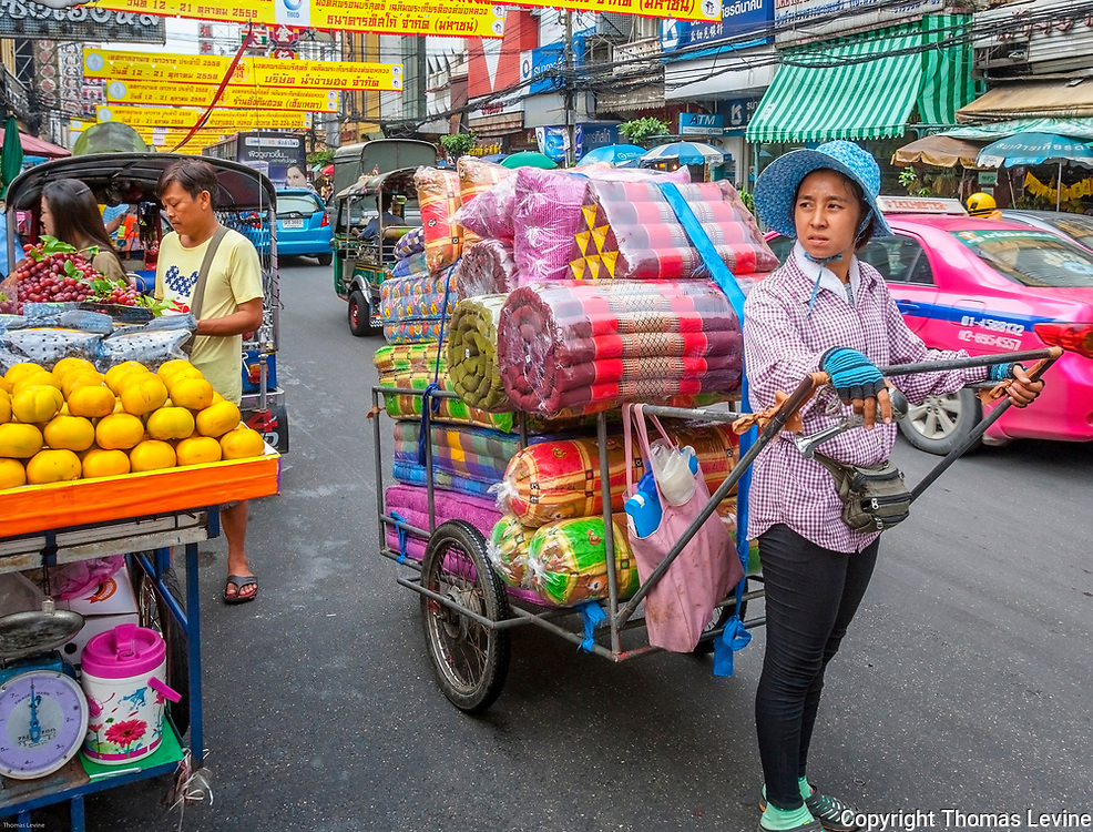 Thai lady pulls cart with for sale goods through Chinatown