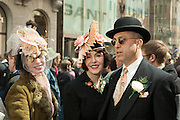 Two women in vintage hats, with a man in a bowler.