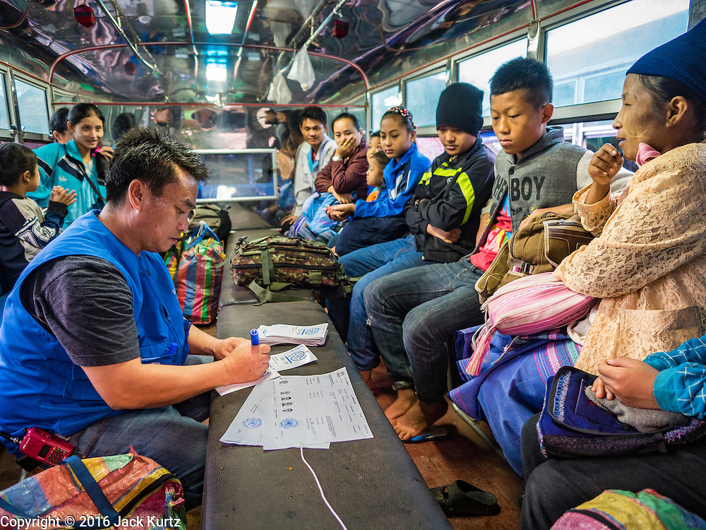 26 OCTOBER 2016 - NUPO TEMPORARY SHELTER, MAE CHAN, TAK, THAILAND:  An IOM (International Organization for Migration) official helps Burmese refugees with last minute paperwork on their bus before they leave the Nupo Temporary Shelter refugee camp. Sixtyfive Burmese refugees living in the Nupo Temporary Shelter refugee camp in Tak Province of Thailand were voluntarily repatriated to Myanmar. About 11,000 people live in the camp. The repatriation was the first large scale repatriation of Myanmar refugees living in Thailand. Government officials on both sides of the Thai / Myanmar border said the repatriation was made possible by recent democratic reforms in Myanmar. There are approximately 150,000 Burmese refugees living in camps along the Thai / Myanmar border. The Thai government has expressed interest several times in the last two years in starting the process of repatriating the refugees.    PHOTO BY JACK KURTZ