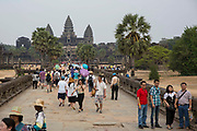 Many tourists walk along the walkway to towards the ancient Angkor Wat temple, Siem Reap, Cambodia.  Angkor Wat is one of UNESCO's world heritage sites. It was built in the 12th century and covers 162 hectares.  It is Cambodia's main tourist attraction.