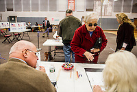 Helga Brunkhardt checks in with Norma Petten and Tom Garfield on voting day at Belmont High School Tuesday morning.  (Karen Bobotas/for the Laconia Daily Sun)