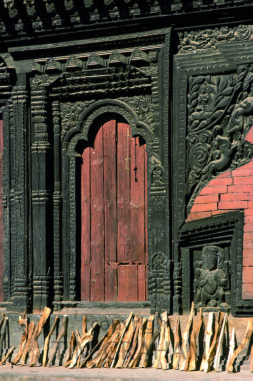 Firewood drying near ornate carved wooden doorway, Bhaktapur, Nepal